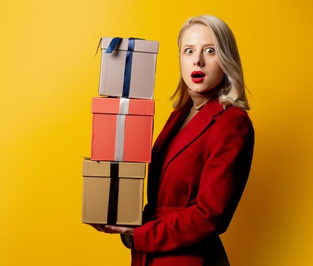 Blonde vrouw in rode jas met geschenkdozen op gele muur