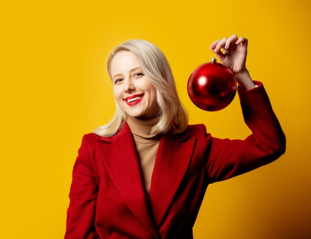 Blonde vrouw in rode jas met kerstbal op gele muur