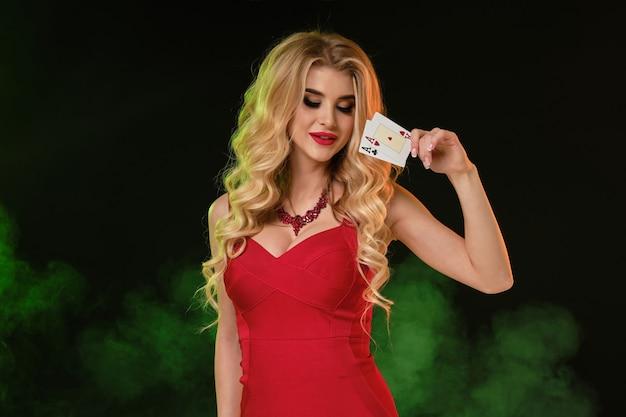 Blonde vrouw in rode jurk en ketting met twee azen glimlachend poseren op kleurrijke rokerige achtergrond...