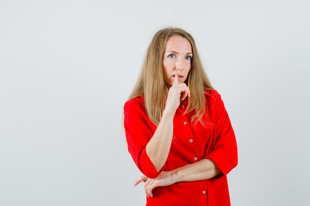Blonde vrouw in rood overhemd vinger op de lippen houden en peinzend kijken,