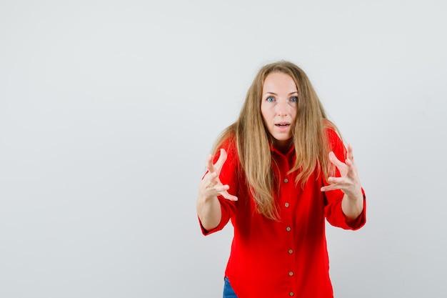Blonde vrouw in rood shirt doet alsof ze iets grijpt en kijkt verbaasd,
