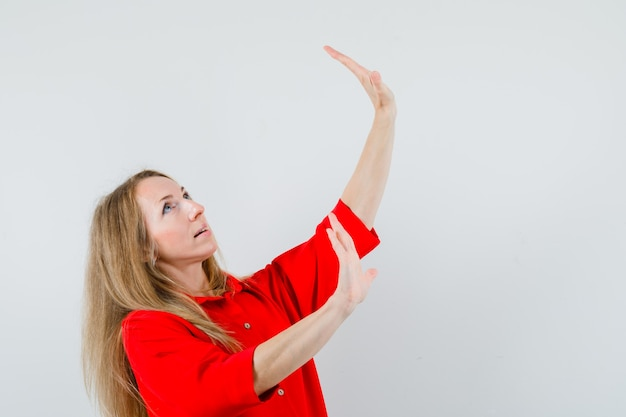 Blonde vrouw in rood shirt handen opheffen op preventieve manier en bang kijken,