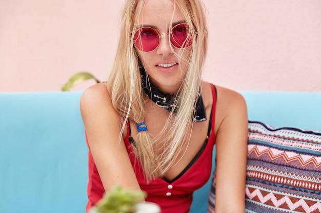 Blonde vrouw in trendy zonnebril, modieuze kleding en rode zonnebril draagt, zit tegen roze muur op comfortabele bank.