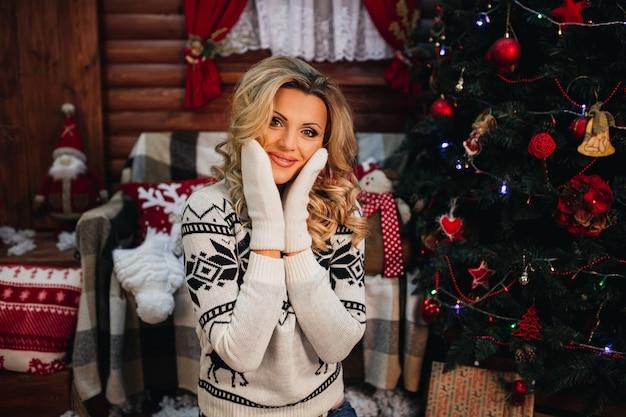 Blonde vrouw in trui handschoenen zittend op de achtergrond van de kerstboom