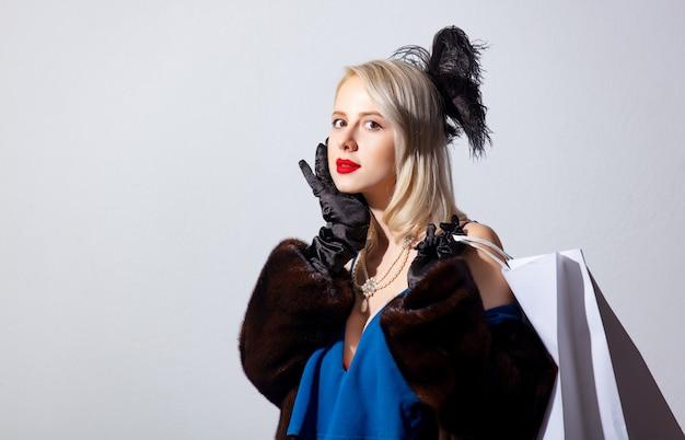 Blonde vrouw in vintage blauwe jurk en bontjas met boodschappentassen