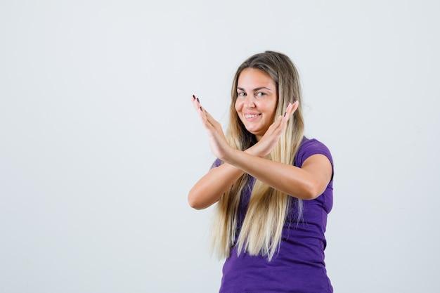 Blonde vrouw in violet t-shirt met stop gebaar en op zoek gelukkig, vooraanzicht.