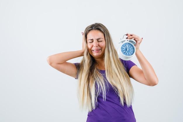 Blonde vrouw in violet t-shirt wekker houden terwijl huilen en op zoek vergeetachtig, vooraanzicht.