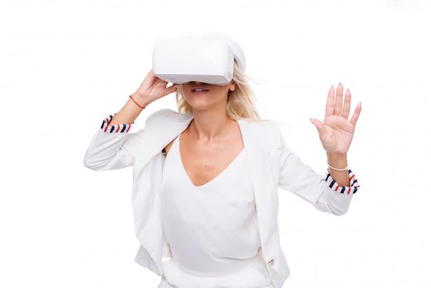 Blonde vrouw in witte suite met virtual reality bril. studio die op witte ruimte is ontsproten