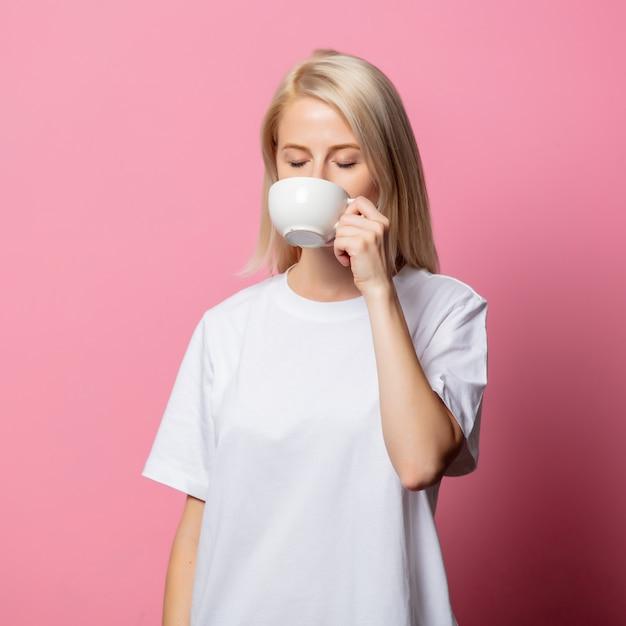 Blonde vrouw in witte t-shirt met kopje koffie