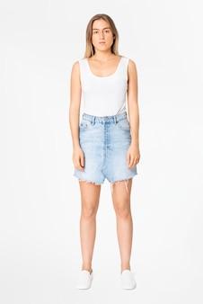 Blonde vrouw in witte tanktop en denim minirok vrijetijdskleding mode full body