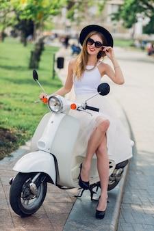 Blonde vrouw in witte tule rok en zwarte hakken zittend op vintage scooter.
