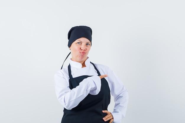 Blonde vrouw in zwart kookuniform wijst naar rechts met wijsvinger, gebogen lippen en ziet er mooi uit