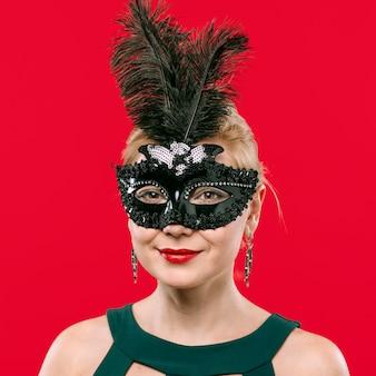 Blonde vrouw in zwart masker met veren