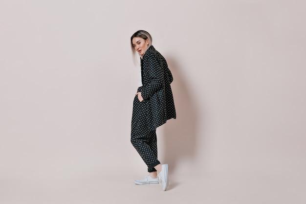 Blonde vrouw in zwart polka dot pak poseren op geïsoleerde muur