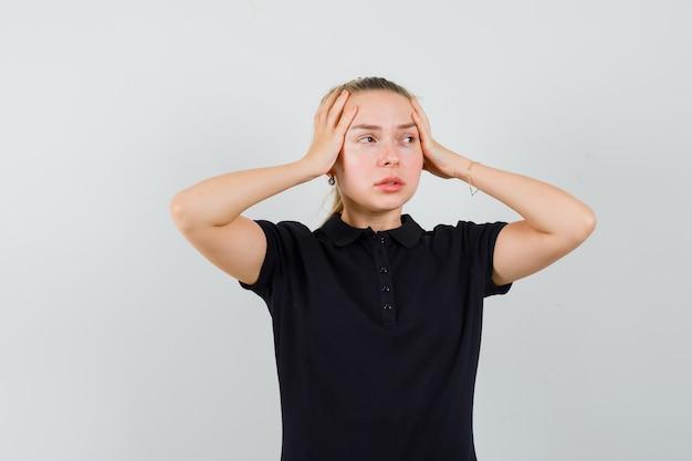 Blonde vrouw in zwart t-shirt houdt haar handen op haar hoofd en kijkt geïrriteerd