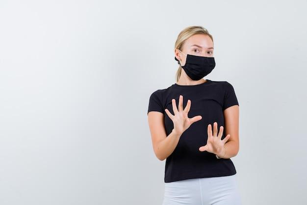 Blonde vrouw in zwart t-shirt, witte broek, zwart masker met stopbord