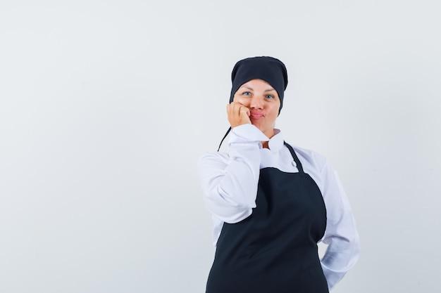 Blonde vrouw in zwarte kok uniform leunende wang aan kant, iets na te denken en er mooi uit