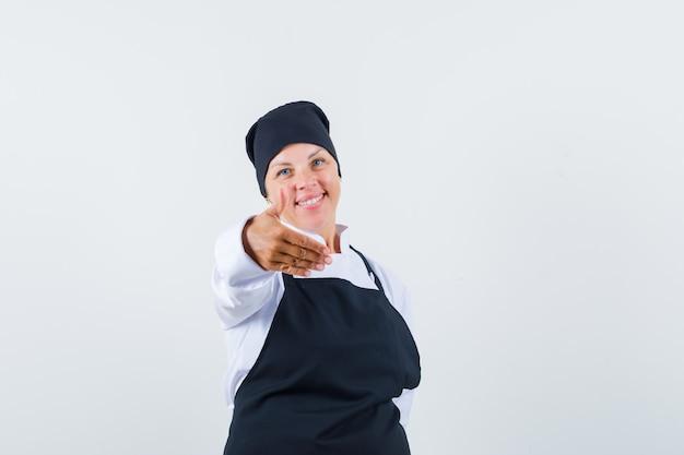 Blonde vrouw in zwarte kok uniforme hand uitrekken naar camera en op zoek naar mooi, vooraanzicht.