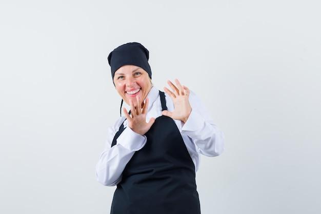 Blonde vrouw in zwarte kok uniforme handen uitrekken als iets tegenhouden en mooi, vooraanzicht kijken.