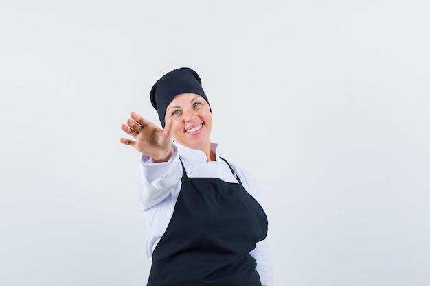 Blonde vrouw in zwarte kok uniforme handen uitrekken naar camera en op zoek naar mooi, vooraanzicht.