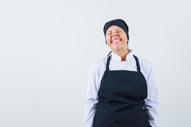 Blonde vrouw in zwarte kok uniforme rechtop staan, gracieus glimlachen en poseren in de camera en op zoek naar mooi, vooraanzicht.