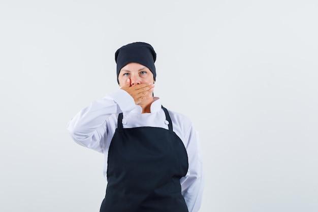 Blonde vrouw in zwarte uniforme kok die mond bedekt met hand en verbaasd, vooraanzicht kijkt.