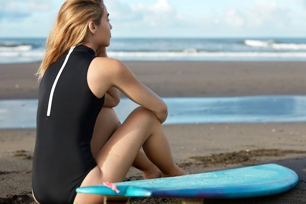 Blonde vrouw in zwembroek met surfplank op strand
