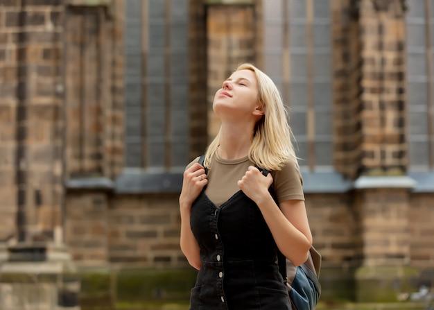 Blonde vrouw is verblijf in de buurt van middeleeuwse kerk in europa
