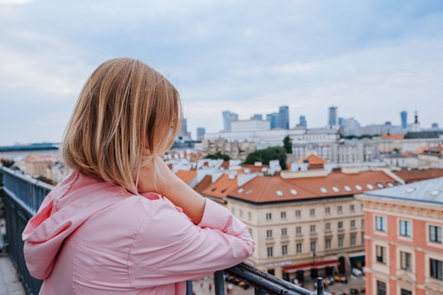 Blonde vrouw kijken naar oude en nieuwe stad in warschau, polen