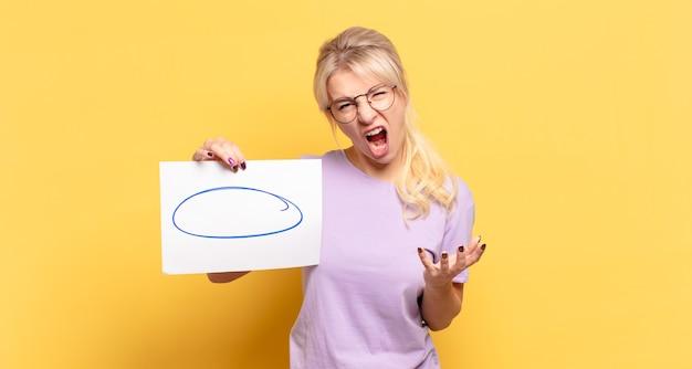Blonde vrouw kijkt boos, geïrriteerd en gefrustreerd schreeuwend wtf of wat is er mis met je