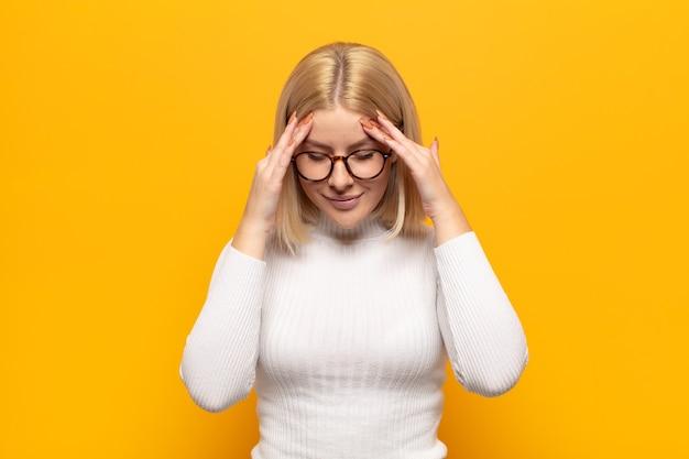 Blonde vrouw kijkt gestrest en gefrustreerd, werkt onder druk met hoofdpijn en kampt met problemen