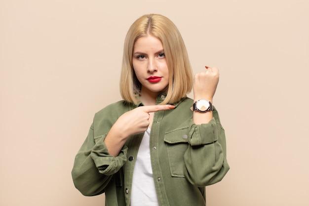 Blonde vrouw kijkt ongeduldig en boos, wijst op horloge, vraagt om stiptheid, wil op tijd zijn