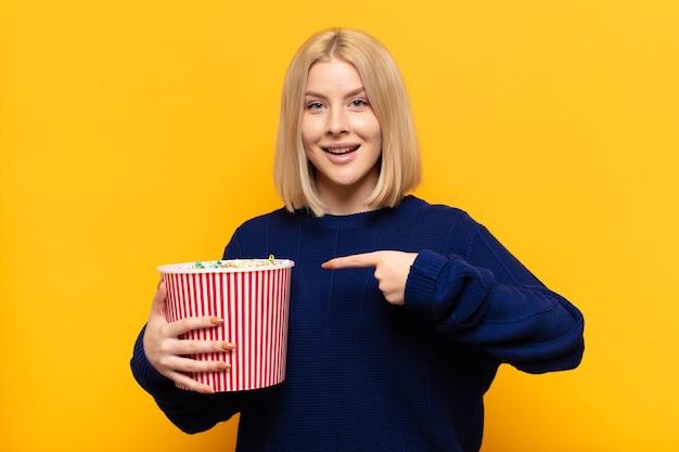 Blonde vrouw kijkt opgewonden en verrast naar de zijkant en naar boven gericht om ruimte te kopiëren