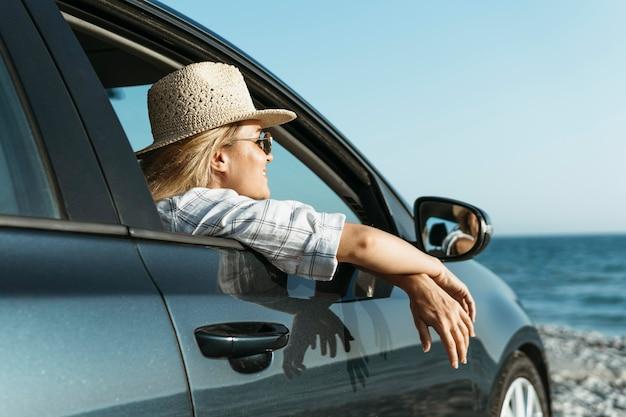 Blonde vrouw kijkt uit autoraam op zoek naar zee