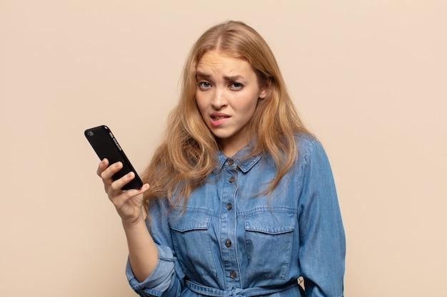Blonde vrouw kijkt verbaasd en verward, lip bijtend met een nerveus gebaar, het antwoord op het probleem niet wetend