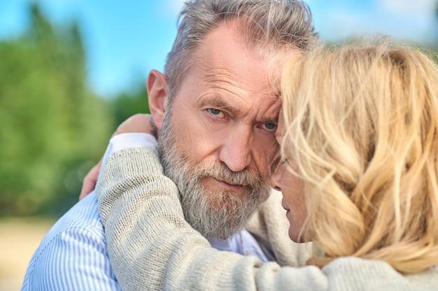 Blonde vrouw knuffelt zelfverzekerde bebaarde man