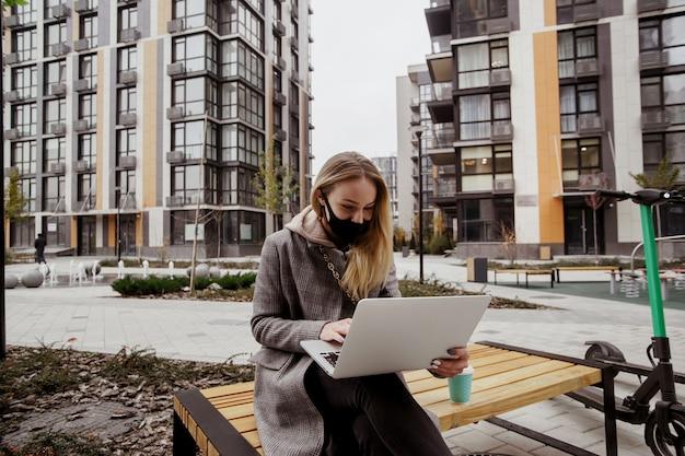Blonde vrouw kwam naar dit park op een elektrische scooter. ze zit op de bank, gebruikt haar moderne laptop en praat via een videogesprek met haar vrienden. zwart medisch gezichtsmasker op haar gezicht. milieuvriendelijke gewoonten.