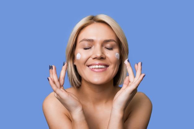 Blonde vrouw lacht en brengt anti-verouderingscrème aan op haar gezicht, poserend op een blauwe muur