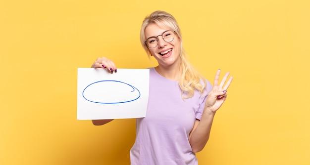 Blonde vrouw lacht en ziet er vriendelijk uit, nummer drie of derde tonend met hand naar voren