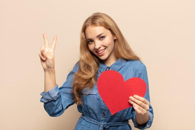 Blonde vrouw lacht en ziet er vriendelijk uit, toont nummer twee of seconde met hand naar voren, aftellend
