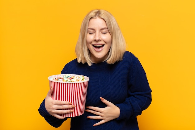 Blonde vrouw lacht hardop om een hilarische grap, voelt zich gelukkig en opgewekt and