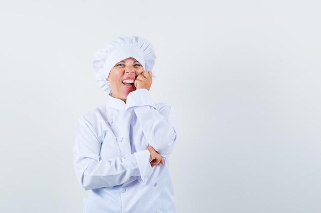 Blonde vrouw leunende wang op palm, glimlachend in witte uniforme kok en ziet er mooi uit.