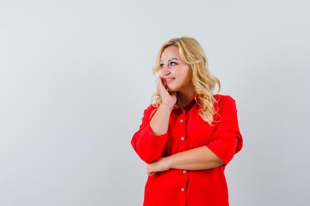 Blonde vrouw leunende wang op palm, wegkijken in rode blouse en op zoek gelukkig, vooraanzicht.