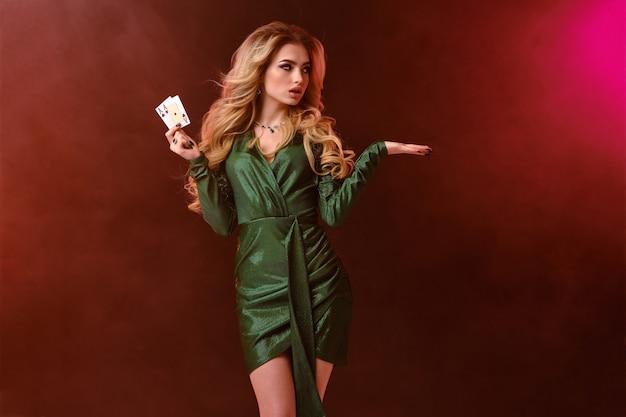 Blonde vrouw, lichte make-up, in groene stijlvolle jurk en sieraden. twee speelkaarten tonen, iets in de hand houden, poseren op kleurrijke rokerige achtergrond, achtergrondverlichting. poker, casino. detailopname