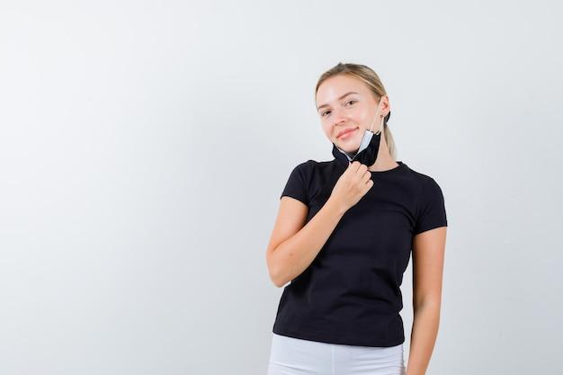 Blonde vrouw masker opstijgen, glimlachend in zwart t-shirt, witte broek