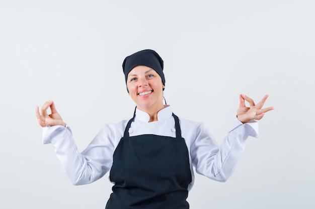 Blonde vrouw meditatie gebaar in zwarte uniforme kok tonen en er mooi uitzien. vooraanzicht.