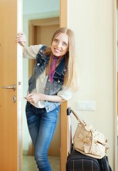 Blonde vrouw met bagage loochende deur