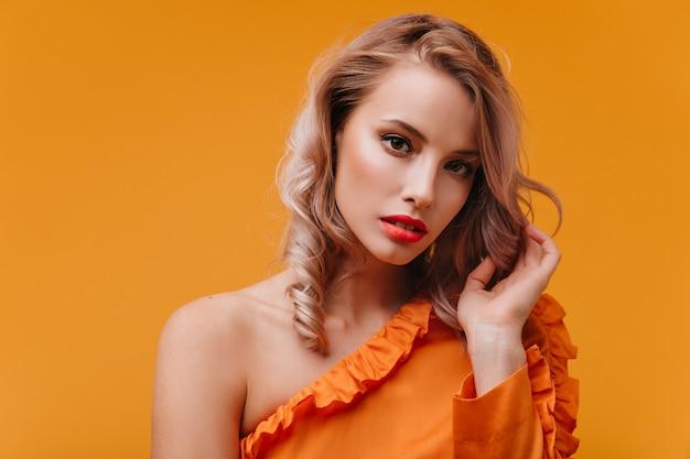 Blonde vrouw met bruine ogen in oranje jurk op zoek naar de voorkant met ernstige gezichtsuitdrukking