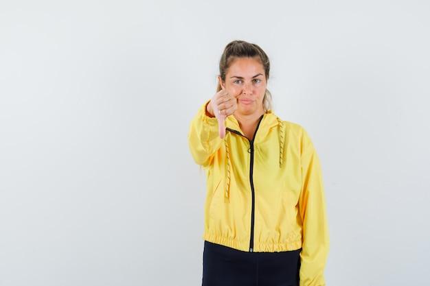 Blonde vrouw met duim naar beneden, grimassen in geel bomberjack en zwarte broek en ontevreden op zoek
