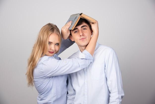 Blonde vrouw met een boek op hoofd brunette man op grijze muur